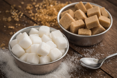 White sugar and brown sugar in bowl on wooden table Stock Photo