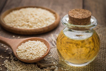 oil seed: Sesame oil in glass jar and sesame seeds on wooden spoon