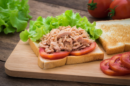 breakfast sandwich: Tuna sandwich with vegetables on wooden plate