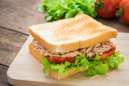 Tuna sandwich with vegetables on wooden plate