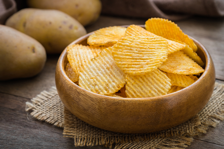 rustic food: Potato chips in bowl and fresh potato Stock Photo