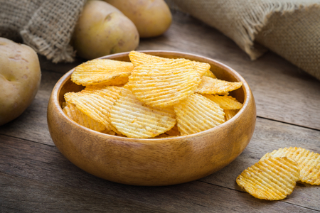 Potato chips in bowl and fresh potato Stock Photo
