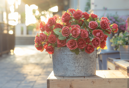 red  light: Bouquet of red roses in bucket on wooden crate, filtered image Stock Photo