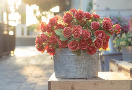 luz roja: Ramo de rosas rojas en un cubo en caja de madera, imagen filtrada Foto de archivo