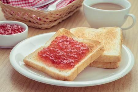 Tostadas con mermelada en un plato y una taza de café, imagen filtrada