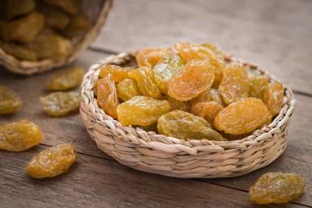 Yellow raisins in little rattan basket Stock Photo