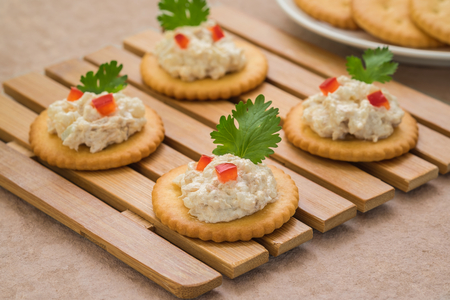 Crackers with tuna salad on wooden plate Stock Photo