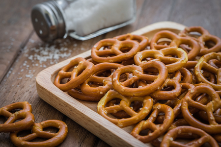 salt shaker: Pretzels on wooden plate and salt shaker