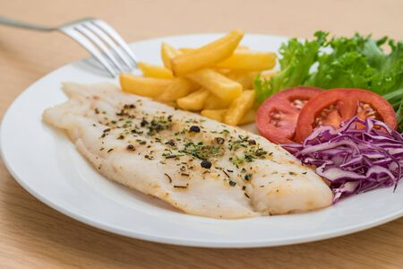 french fries plate: Grilled fish fillet steak with herb and french fries on plate Stock Photo