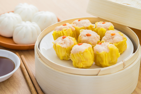 Steamed dumplings in bamboo steamer basket and steamed bun on plate