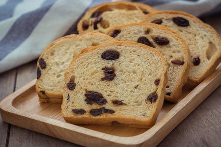 sultanas: Sliced raisin bread on wooden plate