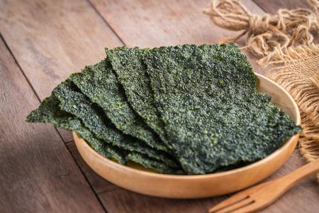 Crispy dried seaweed on wooden plate Stock fotó