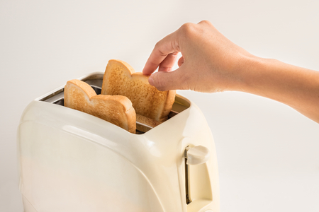 Woman hand taking bread out of a toaster on white background Stock Photo