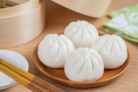 Steamed buns on wooden plate and bamboo steamer basket