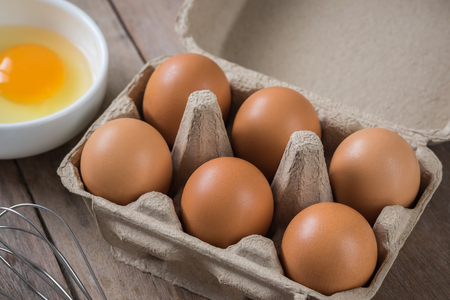 Eggs in carton box and yolk in bowl