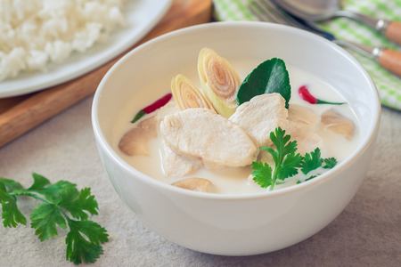 Chicken with coconut milk soup in bowl and rice on plate , Thai food (Tom Kha Kai) Imagens