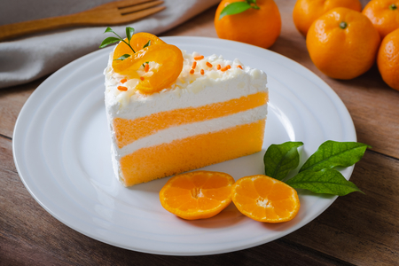 Orange cake and fresh orange on white plate 免版税图像 - 118052697