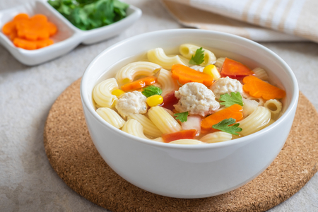 Macaroni chicken meatball soup in bowl