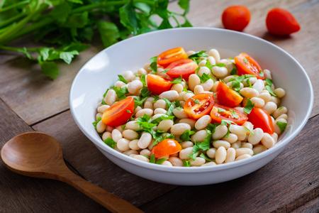 Salade de haricots blancs avec tomates cerises et persil dans un bol
