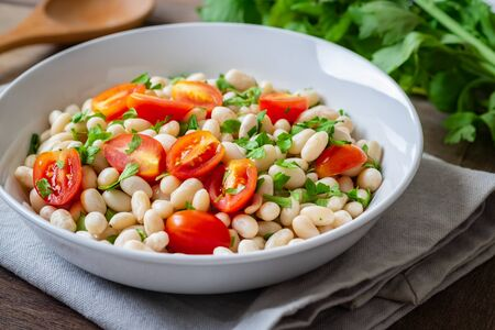 White bean salad with cherry tomatoes and parsley in bowl Stockfoto