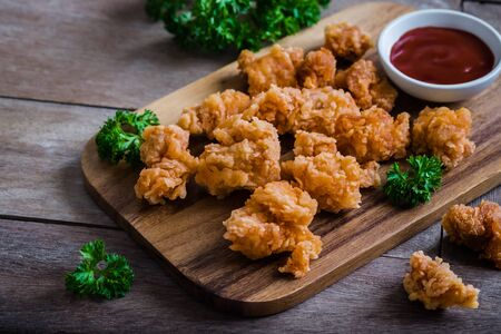 Crispy popcorn chicken on wooden board and dipping sauce Stockfoto
