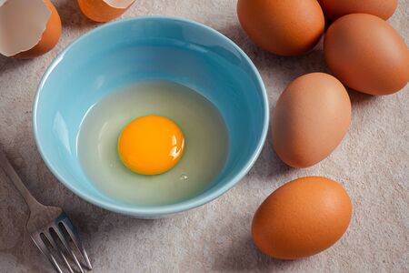 Raw broken egg with yolk in bowl