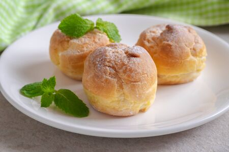 Cream puffs on white plate