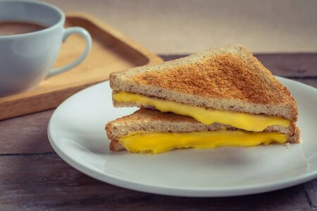 Grilled cheese sandwich on plate and coffee cup