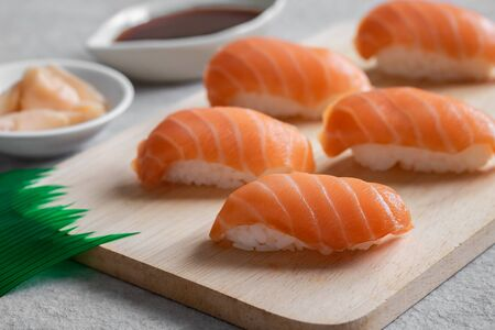 Salmon nigiri sushi on wooden plate, Japanese food