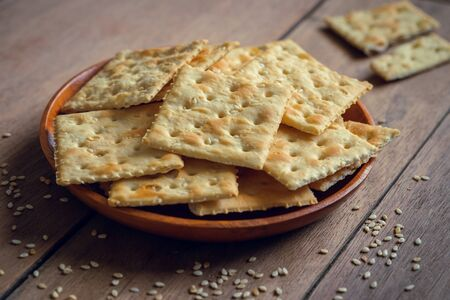 Crispy crackers with sesame on wooden plate