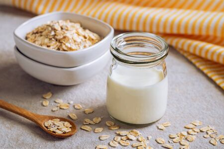 Bottle of oat milk and oat grains in bowl on table