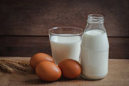 Milk bottle, glass of milk and egg on wooden table Фото со стока