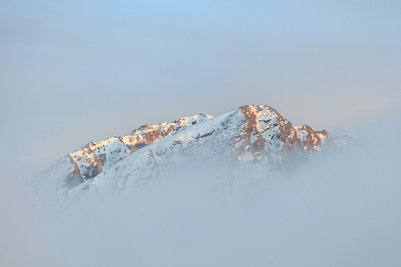 Lonely mountain summit in the clouds - the Himalayas, Langtang, Nepal.
