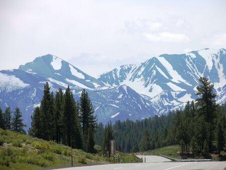 stark: road through mountain area heading toward snow-covered stark alpines Stock Photo