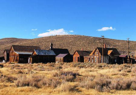 abodes: old weather-beaten mining town wood structures set against blue sky and hill