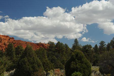 vastness: green tree covered orange mountain against blue sky