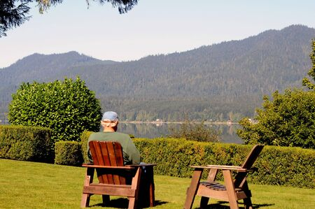 resting: white-haired man relaxing in wooden lawn chair viewing lake