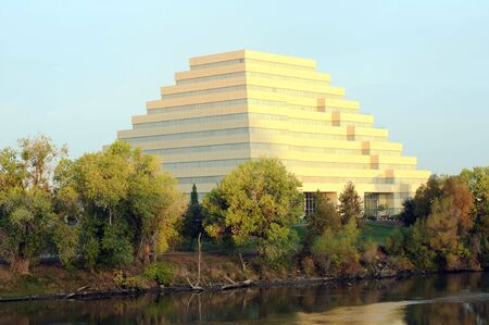 tributary: orange ziggurat building surrounded by trees and blue sky