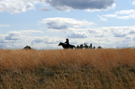 vastness: lone horse rider silhouetted against blue western sky on prairie Stock Photo