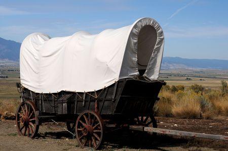 Conestoga wagon gerepliceerd tegen buitenshuis westerse heuvels