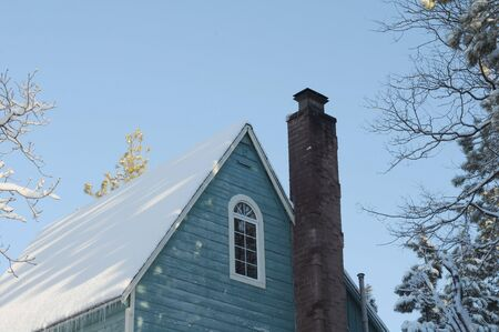 Bucolic mountain cabin roof line covered in snow Stock Photo - 6554391