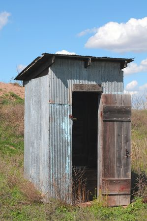 outhouse: old wooden outhouse against hill and blue sky