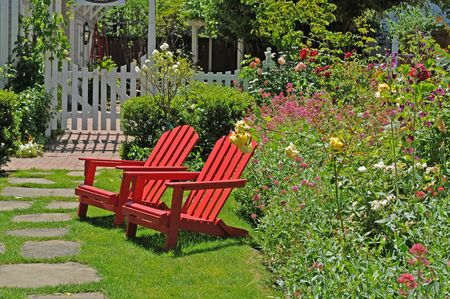 화려한 정원 옆에 앉아있는 두 개의 밝은 빨간 의자