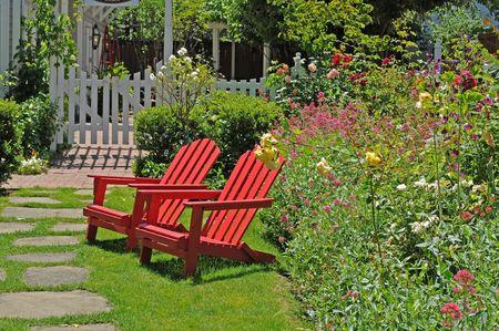 twee heldere rode stoelen zitten door een kleurrijke tuin Stockfoto