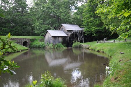 Grayed wooden water mill reflected in pond photo
