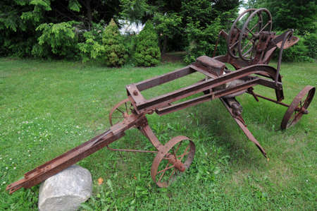 aged tractor frame sits on green grass