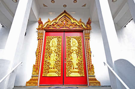 buddhist structures: red Buddhist temple door decorated with gilded figures