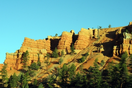 mesas: golden limistone cliffs against blue sky and green trees in foreground Stock Photo