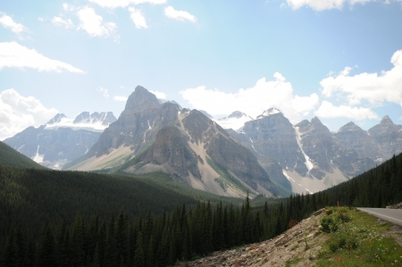 rugged terrain: stark glacier mountains fronted by portion of road Stock Photo