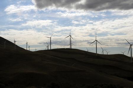 sunup: wind generators sit atop dark hills at cloudy sunrise Stock Photo